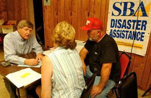 At a temporary office, Small Business Administration (SBA) representative Bobby Knight (L) speaks to a couple about Federal assistance due to flooding. (John Ficara/FEMA photo)